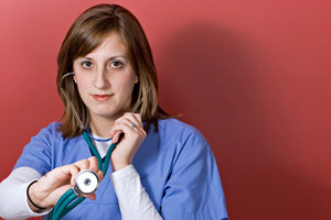 A nurse is holding up her stethoscope over a red background.