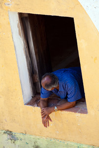 A older balding Hispanic man leans out of a window of an old building.