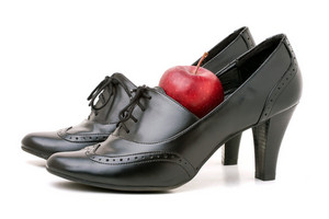 A pair of black leather womens high heel shoes with a red apple sitting inside one of them. A great concept to illustrate educators.