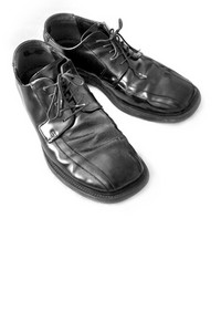 A pair of black mens dress shoes isolated over white - plenty of copy space.