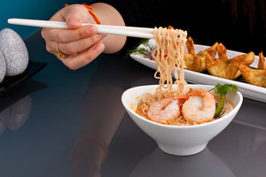 A person eating shrimp and Thai noodles from a bowl with chopsticks along with other appetizer foods.
