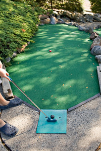 A person getting ready to putt while playing miniature golf.