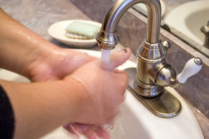 A person washing their hands in the bathroom sink.  Slightly soft - best at smaller sizes.