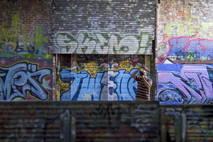 A photographer shooting in an area covered with graffiti.