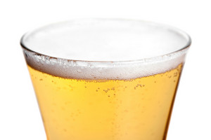 A pilsner glass with golden lager beer isolated over white.  Shallow depth of field.