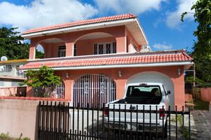 A pink Caribbean style home with a garage and gated driveway.