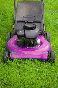 A pink lawn mower cutting through the green grass.