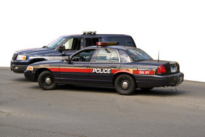 A police car and sport utility vehicle parked in front of a white background.  The clipping path for the white area is included.