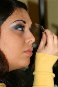 A portrait of a young hispanic woman applying eye makeup.