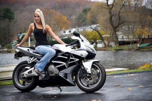 A pretty blonde girl posing on a motorcycle.