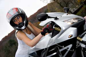 A pretty blonde girl seated on a modern motorcycle.