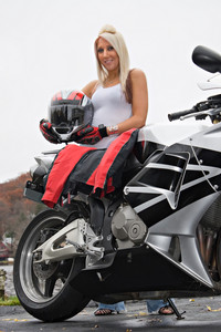 A pretty blonde posing with her motorcycle and riding gear.