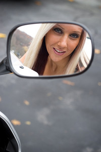 A pretty blonde woman looking into the mirror on her motorcycle.