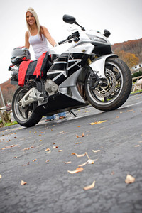 A pretty blonde woman posing with her motorcycle and riding gear.