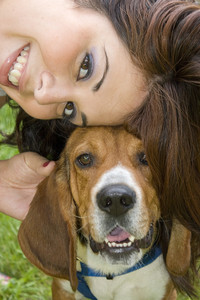 A pretty girl posing with her beagle dog - they both seem to be smiling.