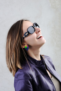 A pretty girl smiling in a  sunglasses on grey background