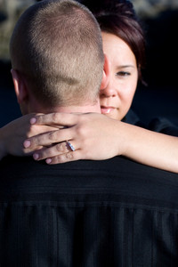 A pretty young woman hugs her husband or fionce.  Shallow depth of field with focus on the diamond engagement ring.