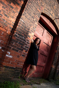 A pretty young woman in a black dress posing in an old doorway.