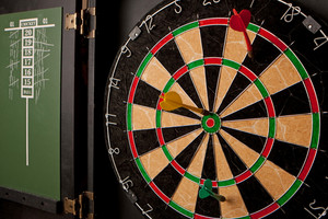 A professional dart board enclosed in a cabinet with slate chalkboard score boards.