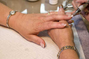 A professional nail technician working on a clients nails with the sander.