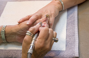 A professional nail technician working on a clients nails.