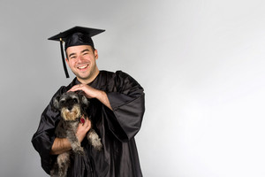 A recent college or high school graduate in his cap and gown holding his pet dog in his arms.
