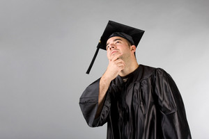 A recent college or high school graduate in his cap and gown thinking and looking contemplative.