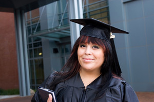 A recent graduate posing in her cap and gown and holding her fresh diploma or degree.
