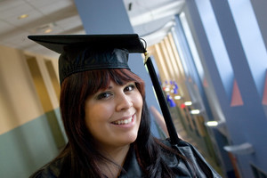 A recent graduate posing in her cap and gown indoors.