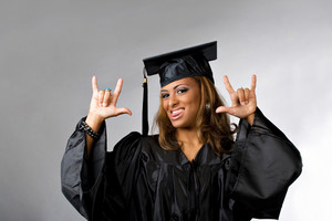 A recent graduate posing in her cap and gown isolated over a silver background.