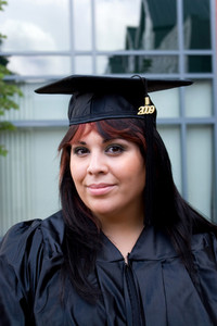 A recent graduate posing in her cap and gown.