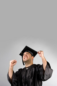 A recent graduate posing in his cap and gown and celebrating. Isolated over a silver background with copy space.