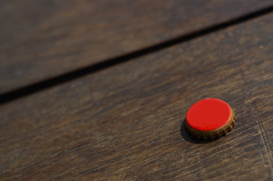 a red bottle cap on wood table