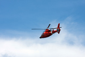 A red helicopter flying over a nice blue sky.