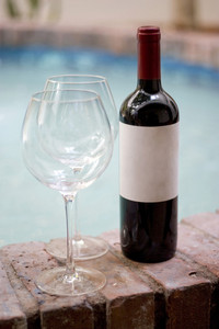 A red wine bottle and two empty glasses by the pool. Plenty of copy space on the blank wine label.
