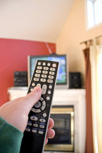 A remote control in hand - shallow depth of field with focus on the remote.