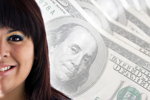 A rich or successful smiling woman in front of a money background with copy space for your text.