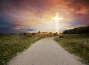 A road leads up to a bright glowing cross.