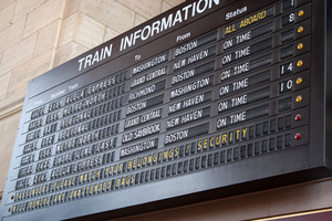 A schedule board in a train station with information telling the time and destinations for travelers.