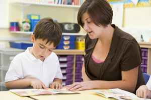 A schoolboy and his teacher reading in a primary class