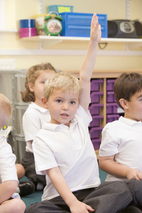 A schoolboy raises his hand in a primary class