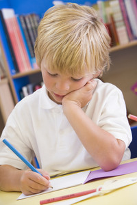 A schoolboy sitting in a primary class