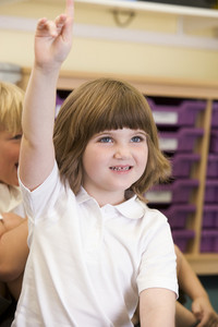 A schoolgirl raises her hand in a primary class