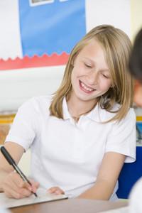 A schoolgirl studying in class