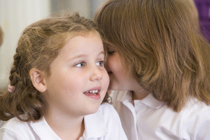 A schoolgirl whispers to her friend in a primary class