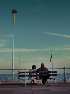 A Senoir Married Couple Sitting On A Bench Against Beach And Sea