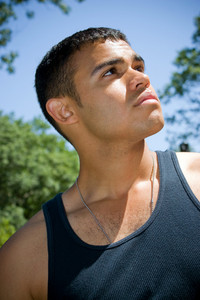 A serious young man wearing dog tags around his neck outdoors.