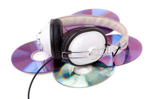A set of headphones atop a pile of compact discs isolated over white.