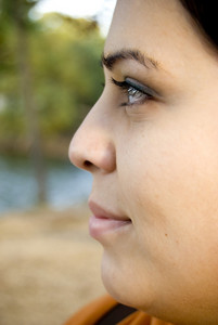 A side profile closeup of a young Spanish womans face.