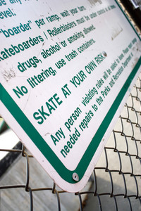 A sign at the skate park clearly states that you will skate at your own risk.  Shallow depth of field.